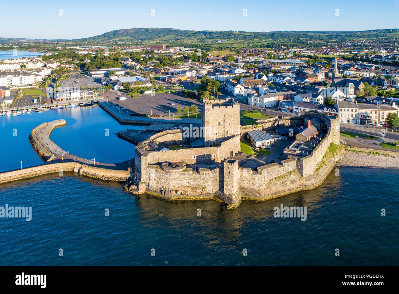 Medieval Norman Castle in Carrickfergus near Belfast in sunrise light. Aerial view with marina, yachts, parking and town - Stock Image