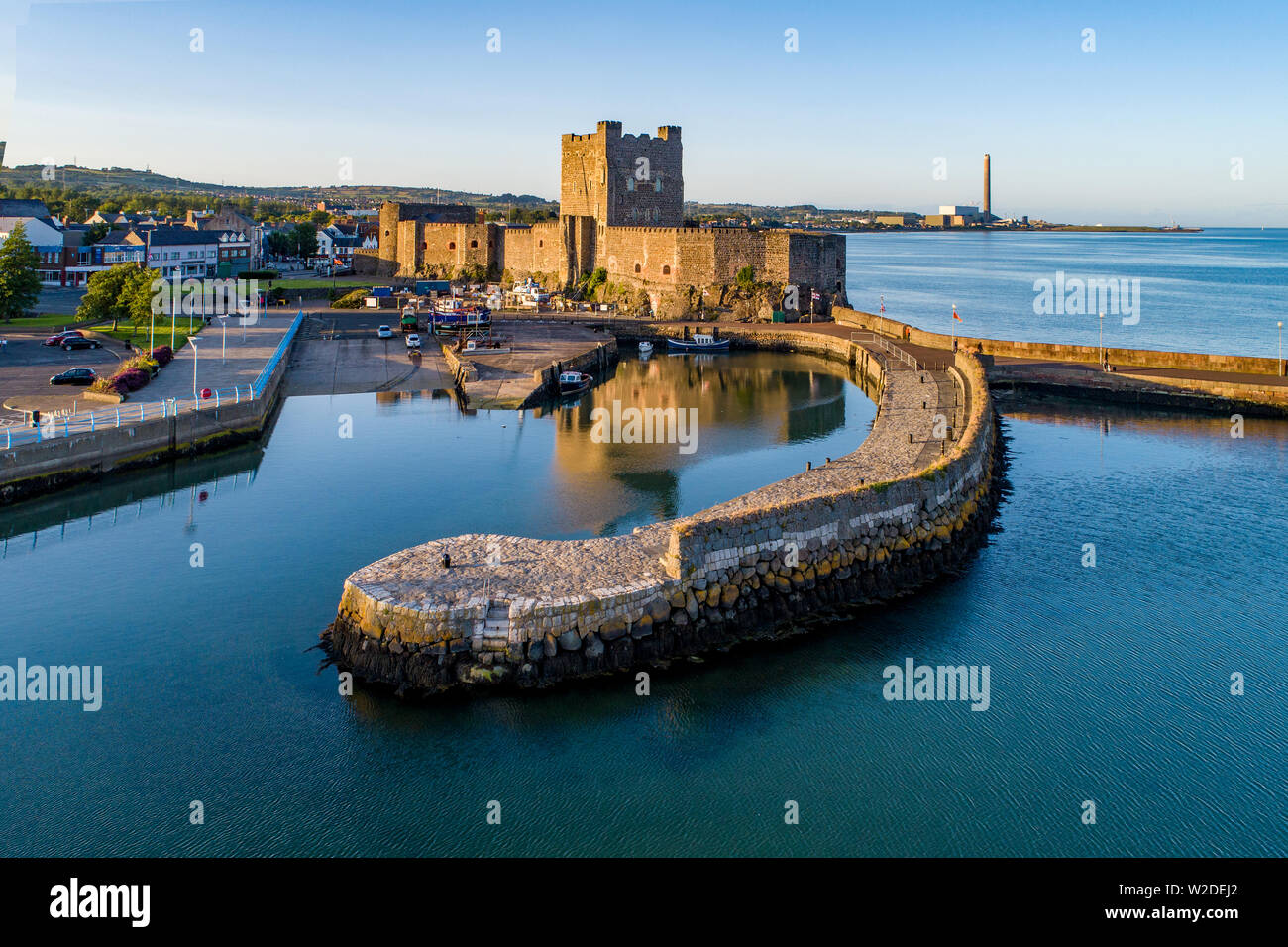 Medieval Norman Castle and harbor in Carrickfergus near Belfast, Northern Ireland, UK. Aerial view  in sunset light. Old power plant in the background - Stock Image