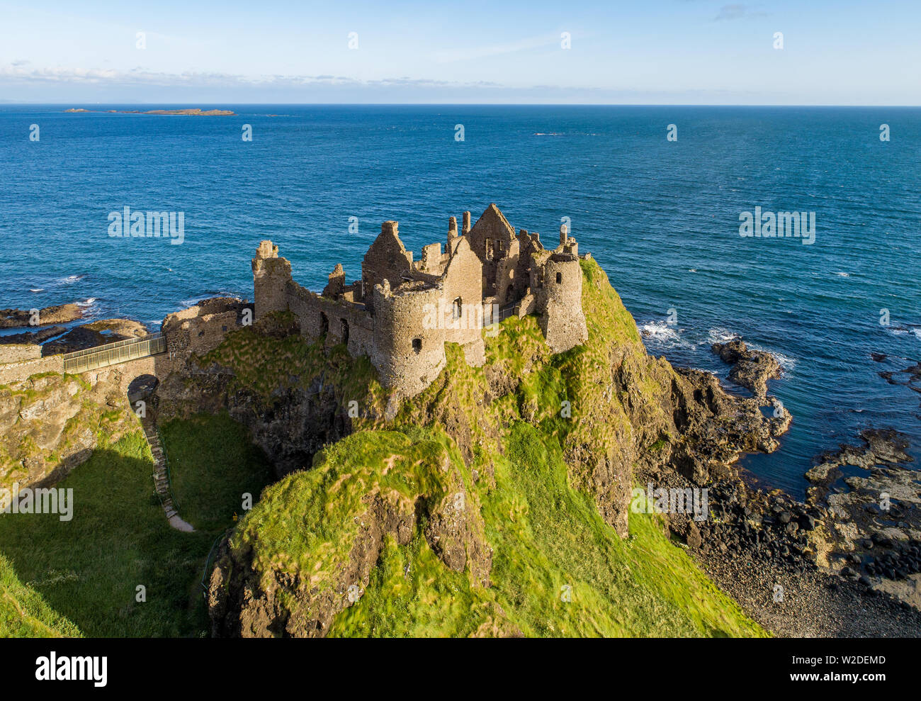 Ruins of medieval Dunluce Castle on a steep cliff. Northern coast of County Antrim, Northern Ireland, UK. Aerial view in sunrise light - Stock Image