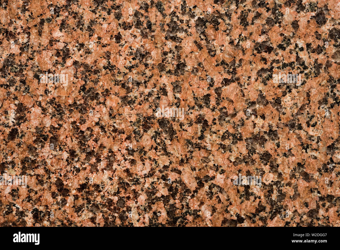 Close up of the flecked surface pattern of polished granite slab. - Stock Image