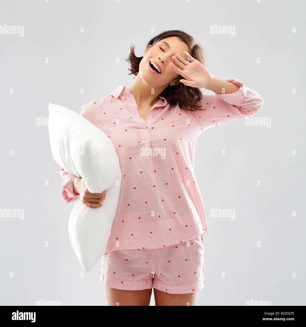 sleepy yawning young woman in pajama with pillow - Stock Image