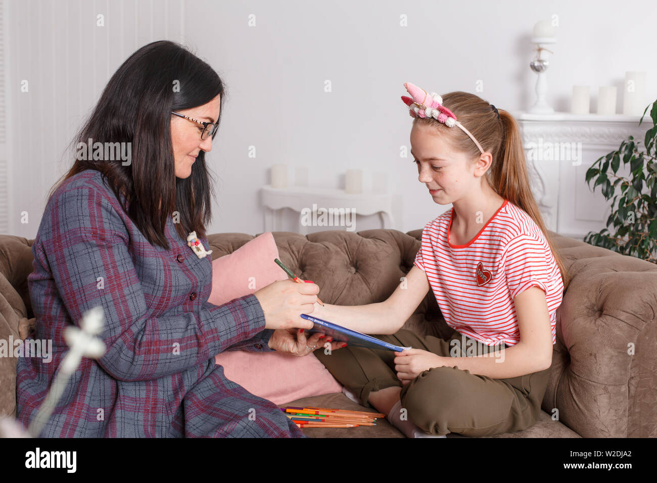 Teen girl on reception at the psychotherapist. Psychotherapy session for children. The psychologist works with the patient. The girl draws pencil with Stock Photo