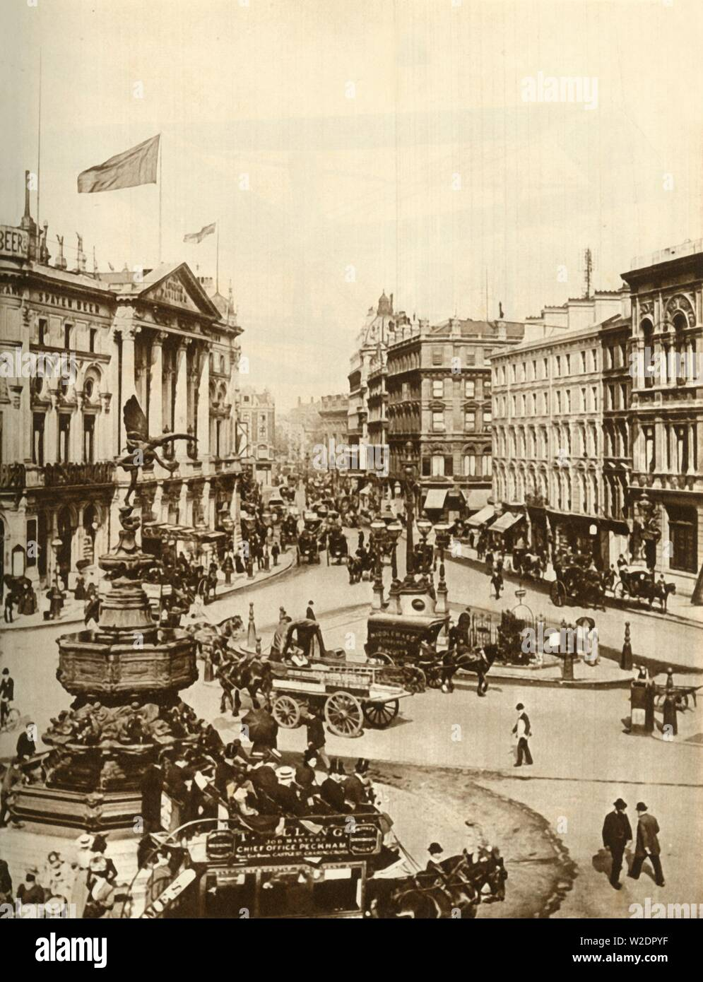 """Statue of Eros at Piccadilly Circus, London, c1910, (1935). Busy thoroughfare in the centre of London, with the London Pavilion theatre on the left, and an open-topped horse-drawn bus in the foreground. From """"The Silver Jubilee Book - The Story of 25 Eventful Years in Pictures"""". [Odhams Press Ltd., London, 1935] - Stock Image"""