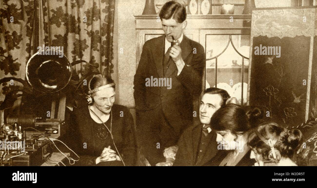 """A family listening to the results of the general election of 1923, (1935). 'Wireless brought the election results into the homes of the people, enabling them to get the very latest results in the privacy and comfort of their own fireside.' From """"The Silver Jubilee Book - The Story of 25 Eventful Years in Pictures"""". [Odhams Press Ltd., London, 1935] - Stock Image"""