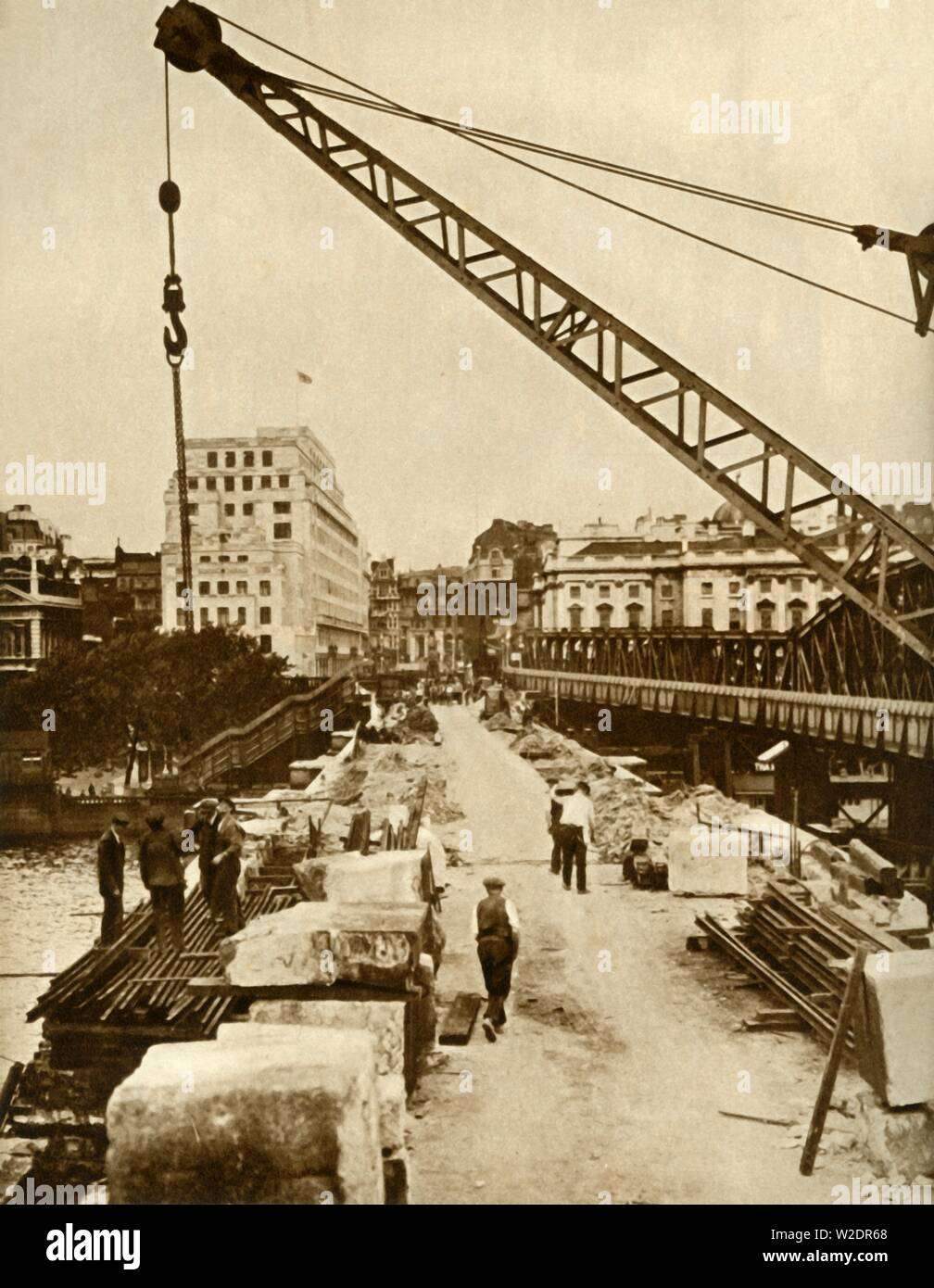"The rebuilding of Waterloo Bridge, London, 1934, (1935). London County Council demolished the old bridge which was damaged, and commissioned a new structure designed by Sir Giles Gilbert Scott. The project was placed on hold due to the Second World War. The only Thames bridge to have been damaged by German bombers during the war, it was not fully completed until 1945. From ""The Silver Jubilee Book - The Story of 25 Eventful Years in Pictures"". [Odhams Press Ltd., London, 1935] - Stock Image"