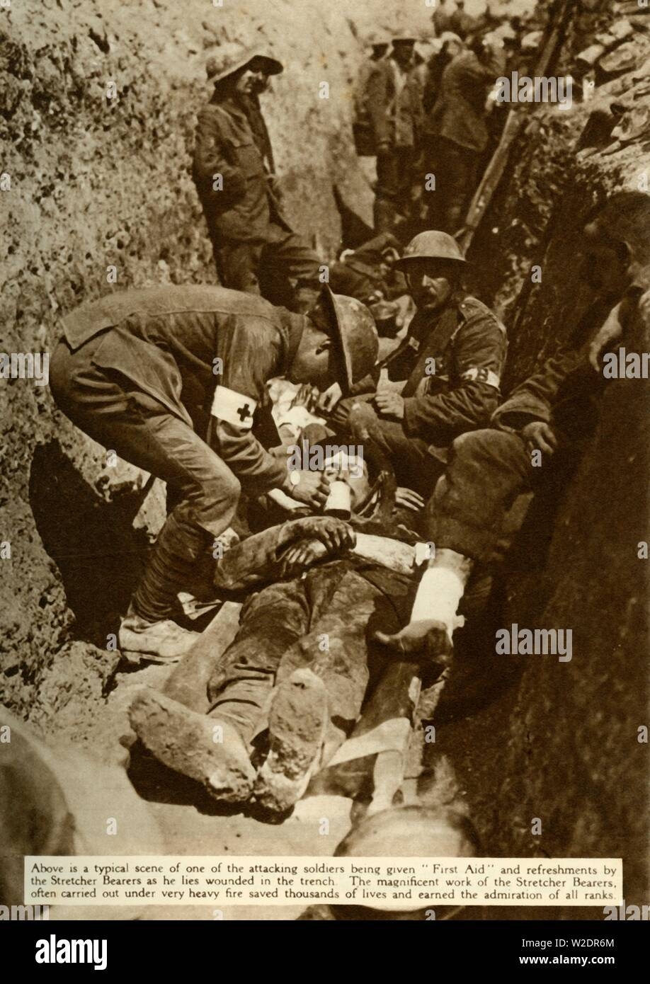 """Wounded British soldier being treated in the trenches during the Battle of the Somme, First World War, 1916, (1935). 'One of the attacking soldiers being given """"First Aid"""" and refreshments by the Stretcher Bearers as he lies wounded in the trench. The magnificent work of the Stretcher Bearers, often carried out under very heavy fire, saved thousands of lives and earned the admiration of all ranks.' From """"The Silver Jubilee Book - The Story of 25 Eventful Years in Pictures"""". [Odhams Press Ltd., London, 1935] - Stock Image"""
