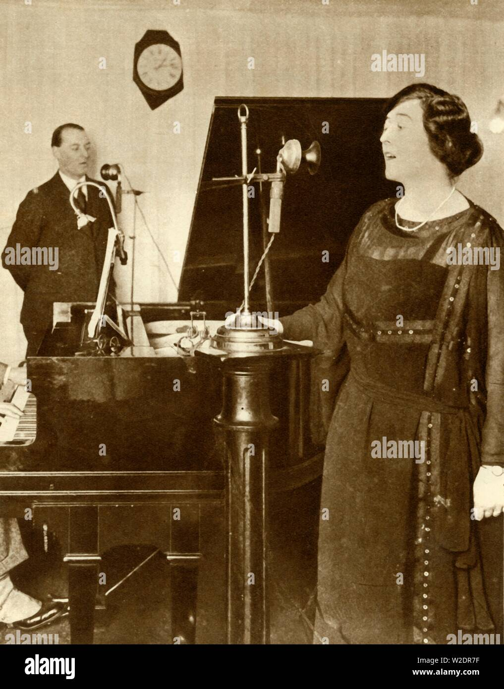 """Performers singing a duet in one of the studios of 2LO, Savoy Hill, London, 1923, (1935). 2LO was the second radio station to broadcast regularly in the United Kingdom. It began broadcasting in May 1922, and in November that year the station was transferred to the new British Broadcasting Company. From """"The Silver Jubilee Book - The Story of 25 Eventful Years in Pictures"""". [Odhams Press Ltd., London, 1935] - Stock Image"""