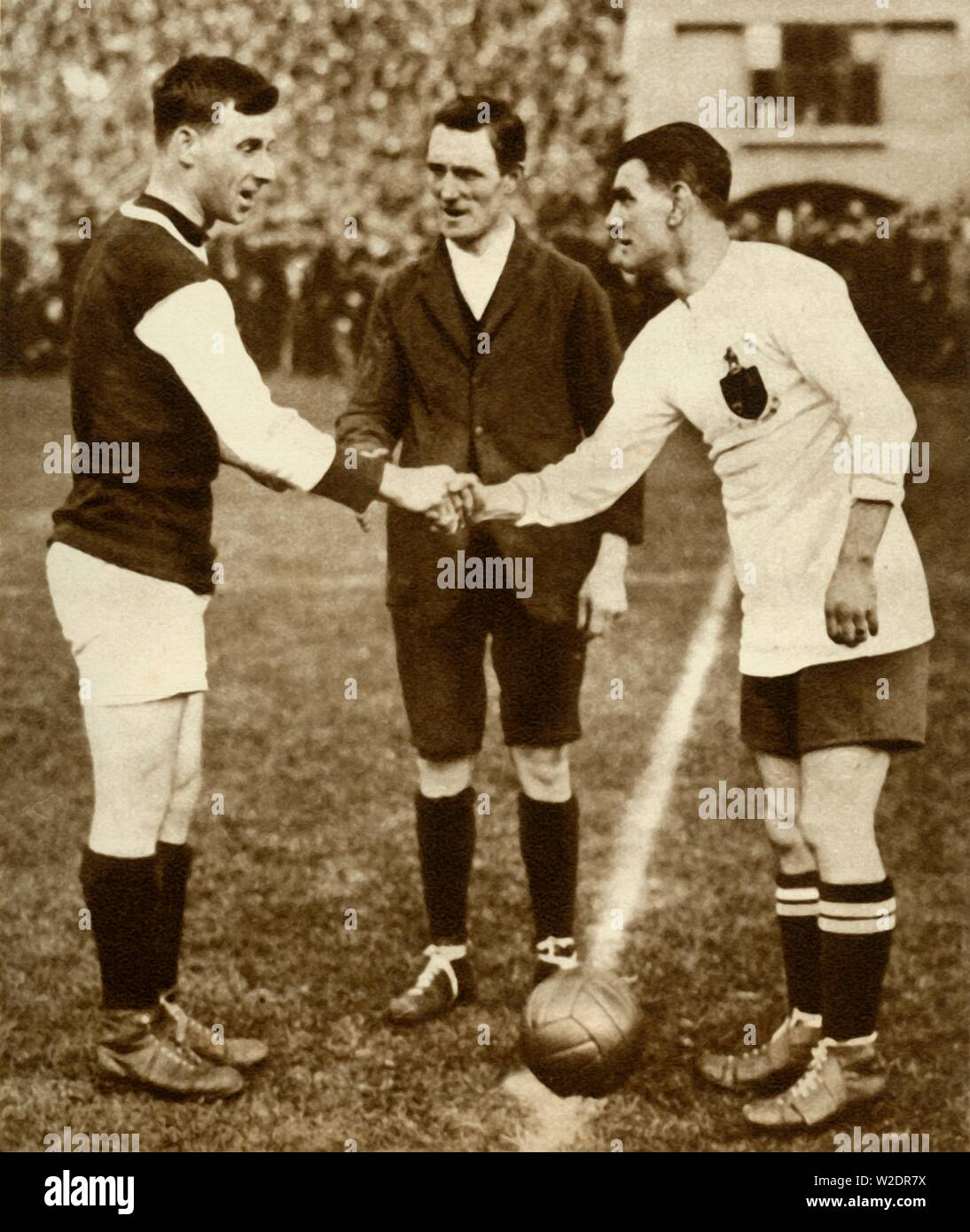 """George Kay and Joe Smith shake hands before kick-off, FA Cup Final, Wembley Stadium, London, 28 April 1923, (1935). George Kay (1891-1954), captain of West Ham United, shaking hands with Joe Smith (1889-1971), the Bolton Wanderers' captain, as the first FA (Football Association Challenge Cup) Final is held at the new Wembley Stadium. Bolton Wanderers beat West Ham 2-0. From """"The Silver Jubilee Book - The Story of 25 Eventful Years in Pictures"""". [Odhams Press Ltd., London, 1935] - Stock Image"""