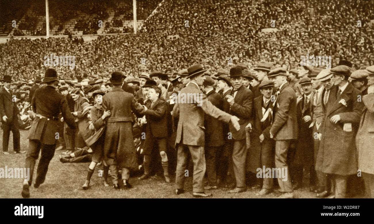 """The first FA Cup Final is held at the new Wembley Stadium in London, 28 April 1923, (1935). Police trying to keep the crowds back at the first Football Association Challenge Cup final match between Bolton Wanderers and West Ham United. 'The crowds were so enormous that they broke down the barriers and the police had to form cordons to prevent spectators overflowing on to the ground.' From """"The Silver Jubilee Book - The Story of 25 Eventful Years in Pictures"""". [Odhams Press Ltd., London, 1935] - Stock Image"""