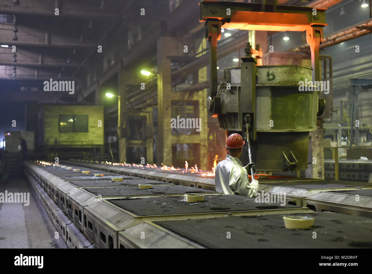 Workers in protective equipment in a foundry during the production of steel components - workplace industrial factory Stock Photo