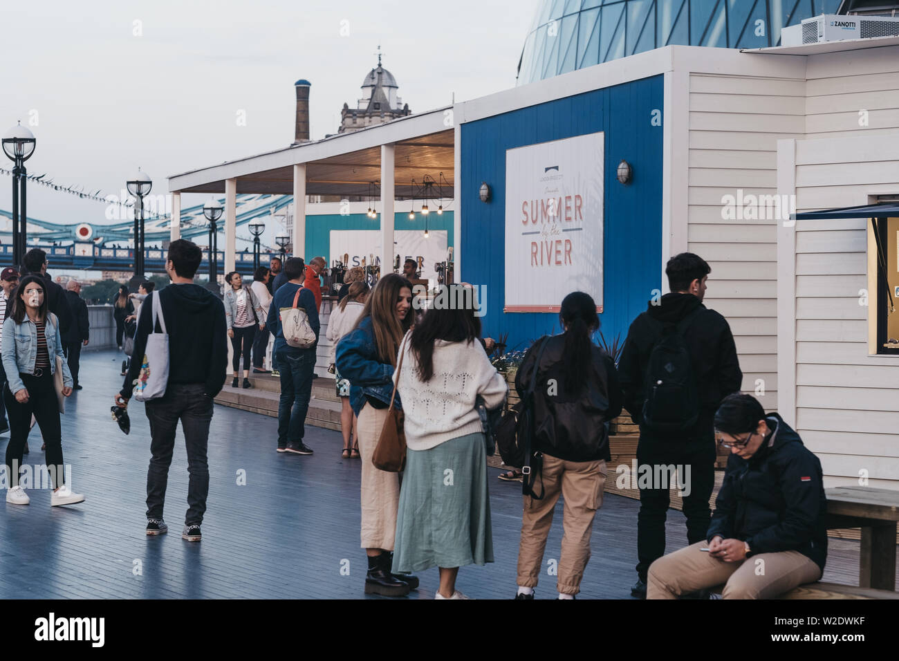 London, UK - June 22, 2019: People at the Summer by the River open air festival taking place in 2019 in London Bridge, London. During blue hour, selec - Stock Image