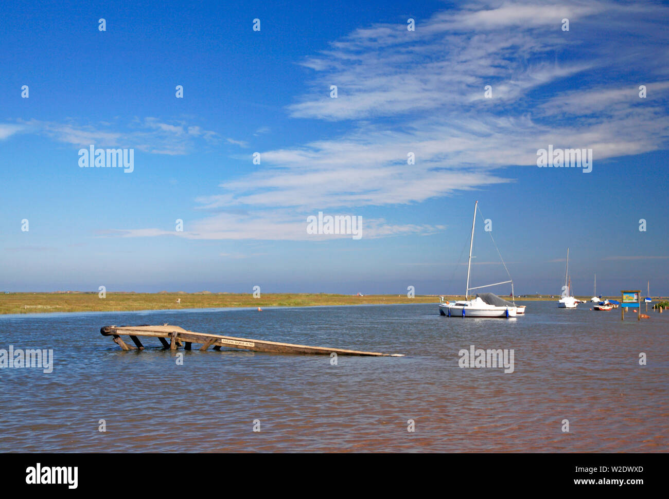 A view of yachts anchored in the channel to the harbour at flood tide in North Norfolk at Blakeney, Norfolk, England, United Kingdom, Europe. - Stock Image