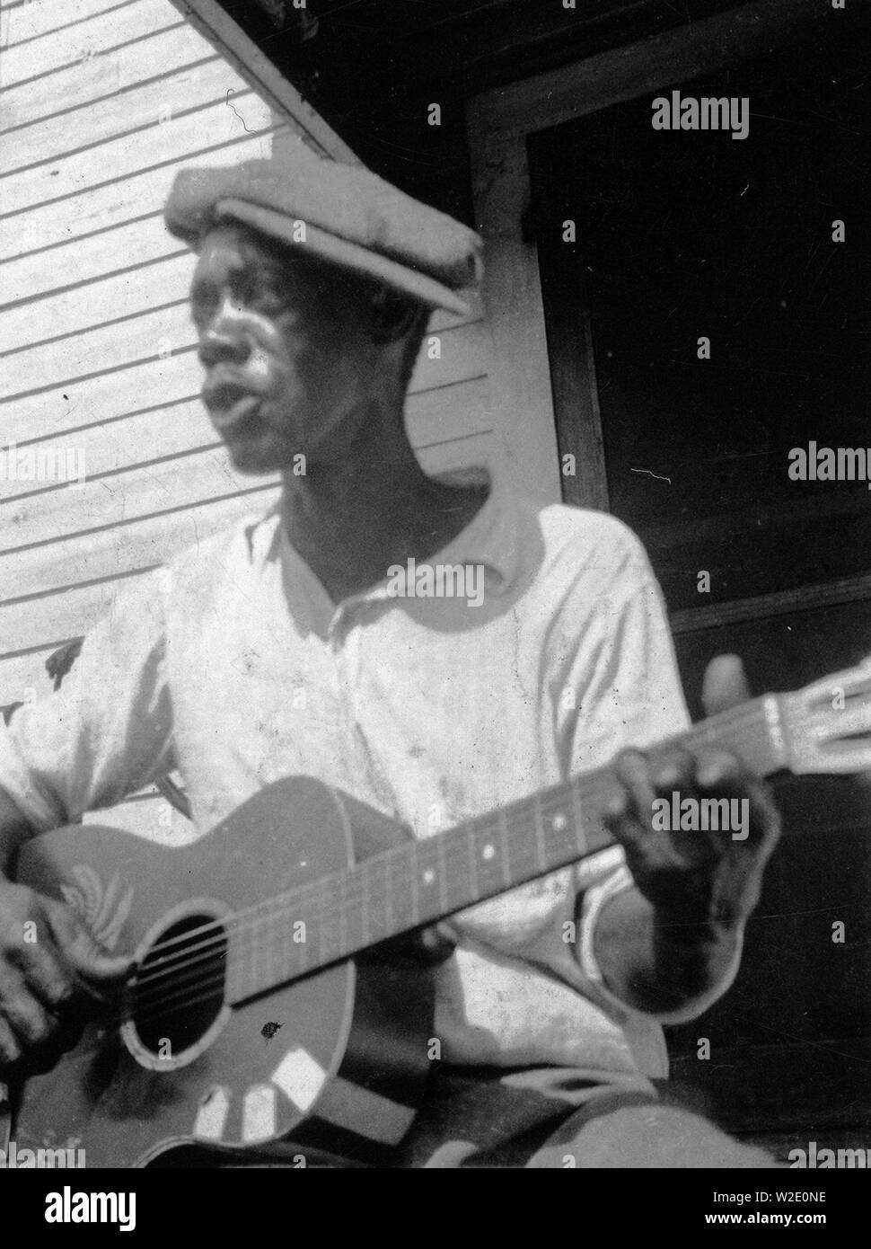 Bill Tatnall, half-length portrait, seated, facing left, playing guitar, Frederica, Georgia ca. June 1935 - Stock Image