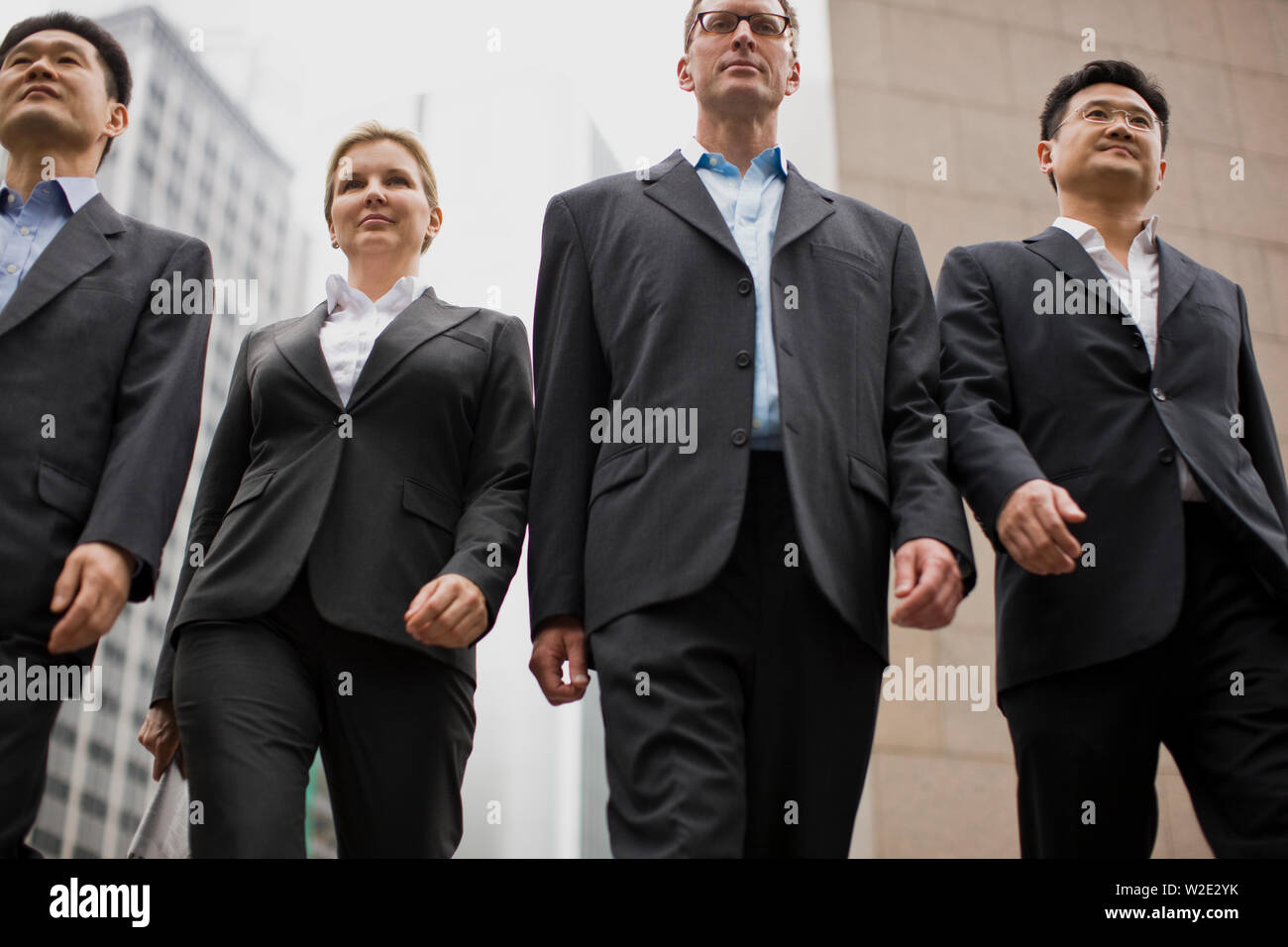 Four confident businesspeople walking side by side through the city. - Stock Image
