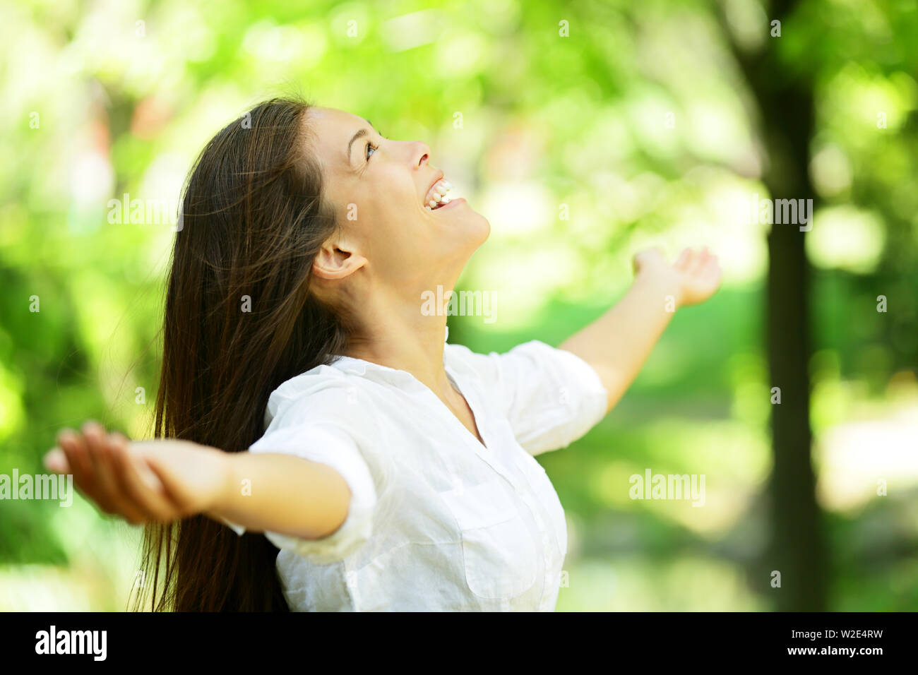 Attractive young woman rejoicing in a spring or summer garden standing sideways with her arms outstretched and her head raised to the heavens enjoying the freshness and beauty of nature - Stock Image