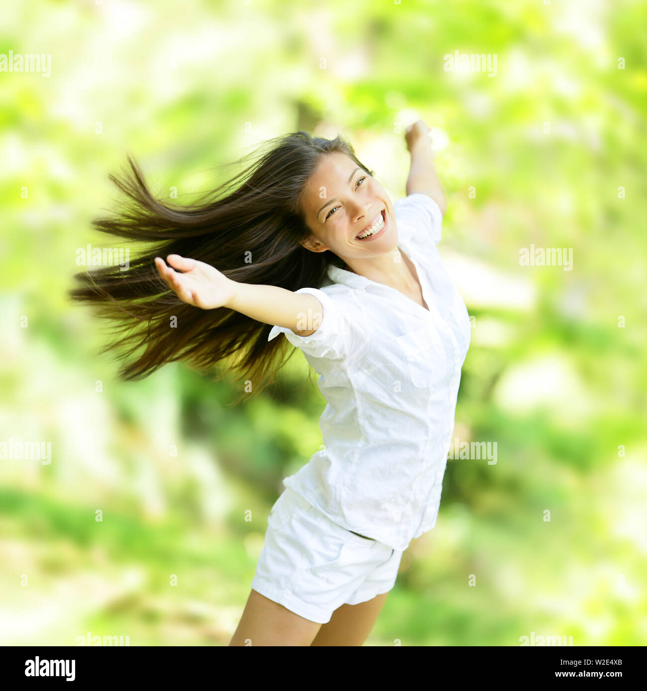 Rejoicing happy woman in flying motion smiling full of joy and vitality in summer or spring forest. Eurasian female model. - Stock Image