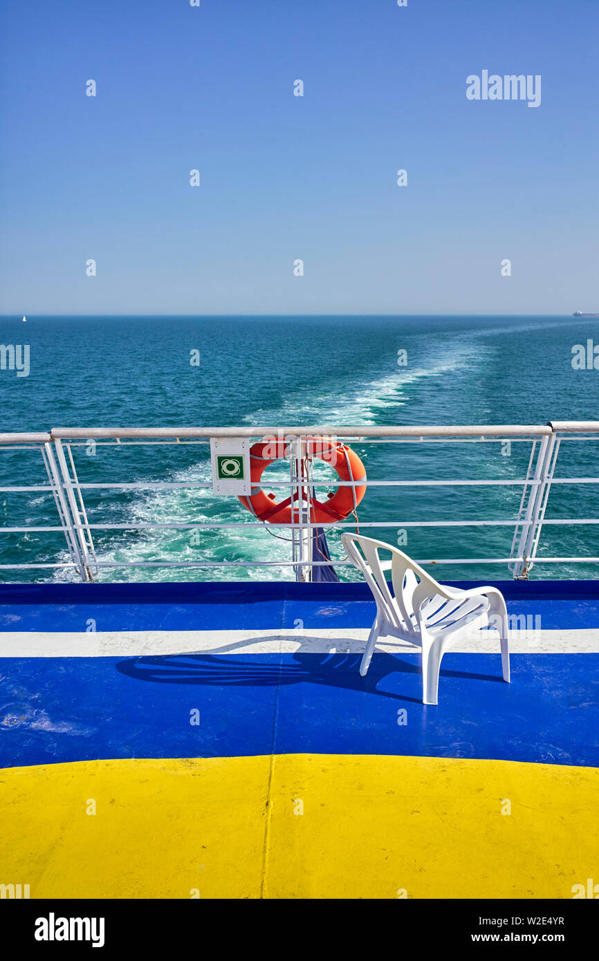 A plastic chair on the rear deck of a cross channel ferry coming into the UK from Brittany - Stock Image