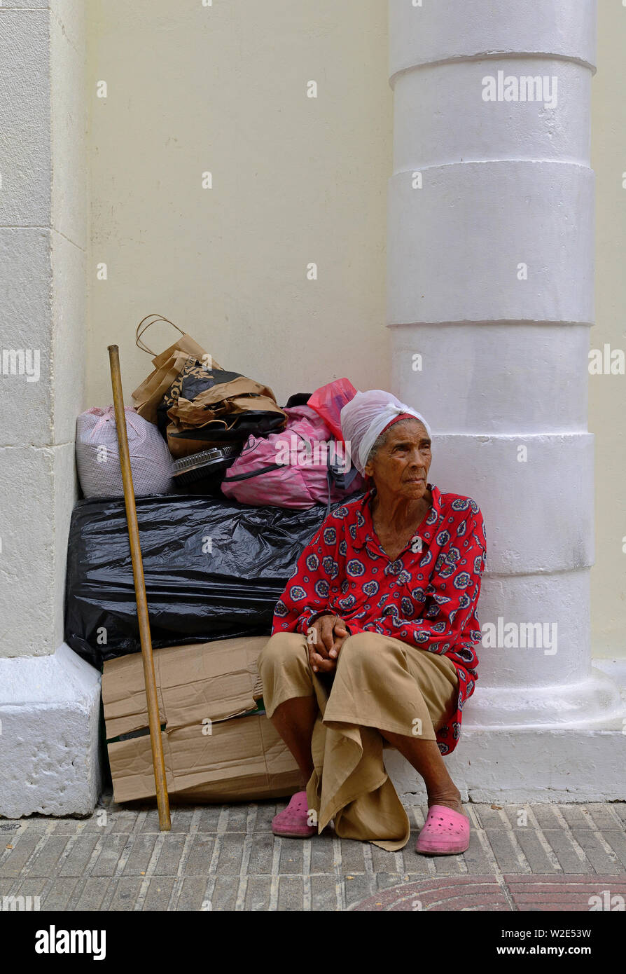 santo domingo, dominican republic - november 01, 2013: an old woman sitting on the roadside of calle el conde - Stock Image