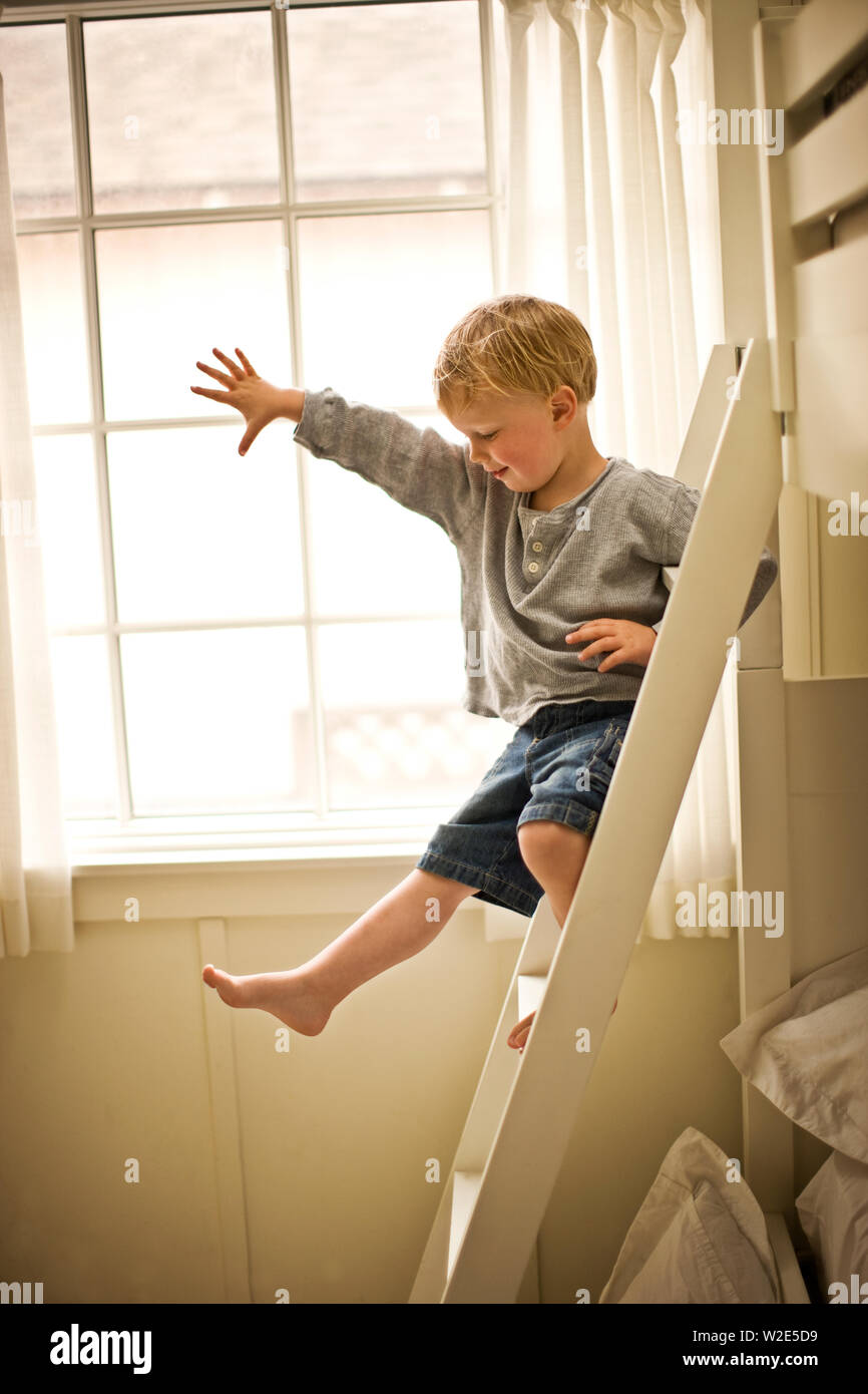 Picture of: Little Boy Climbing Down His Bunk Bed Ladder Stock Photo Alamy