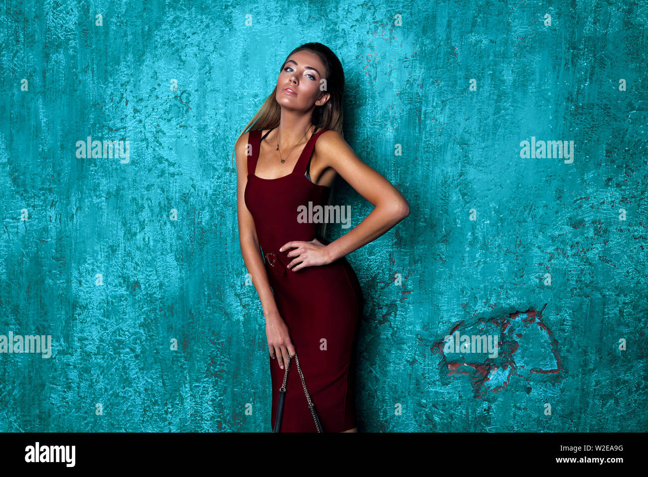 Passion girl with long blonde hair demonstrate new stylish burgundy dress. Slim perfect body, bronze skin, long arms. Fashionable look, beautiful face Stock Photo