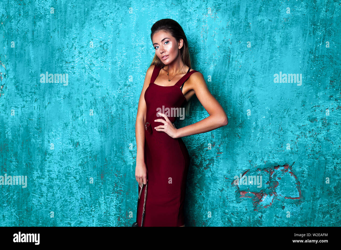 Fashionable young girl standing in a studio, shooting on the blue wall background. Burgundy dress with open arms and waist belt. Stylish hair, bright Stock Photo