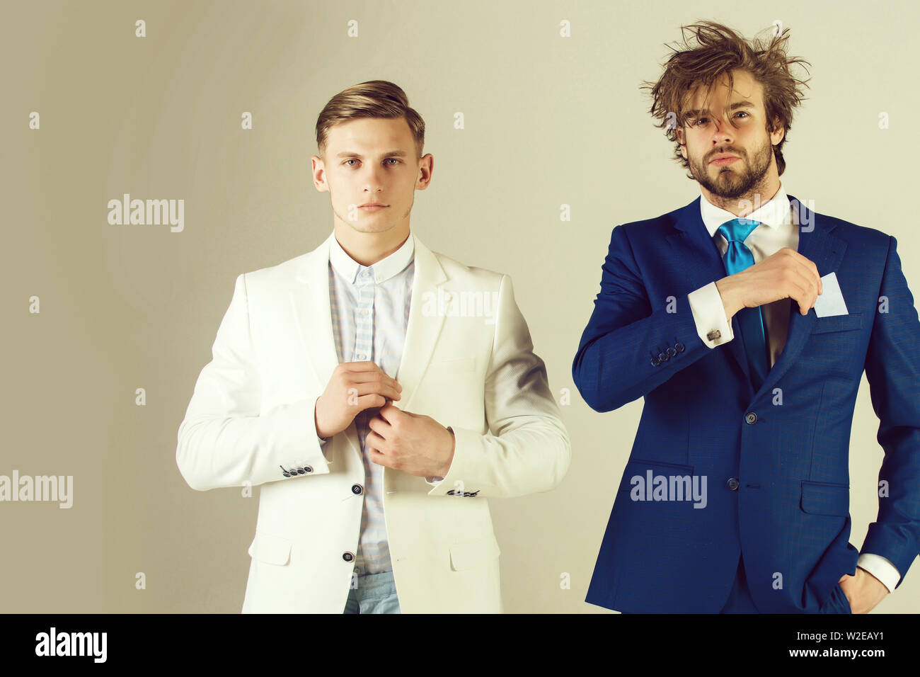 Two businessmen standing on grey background. Man with shaven face wearing white jacket. Macho with beard putting card in pocket. Business ethics and i - Stock Image