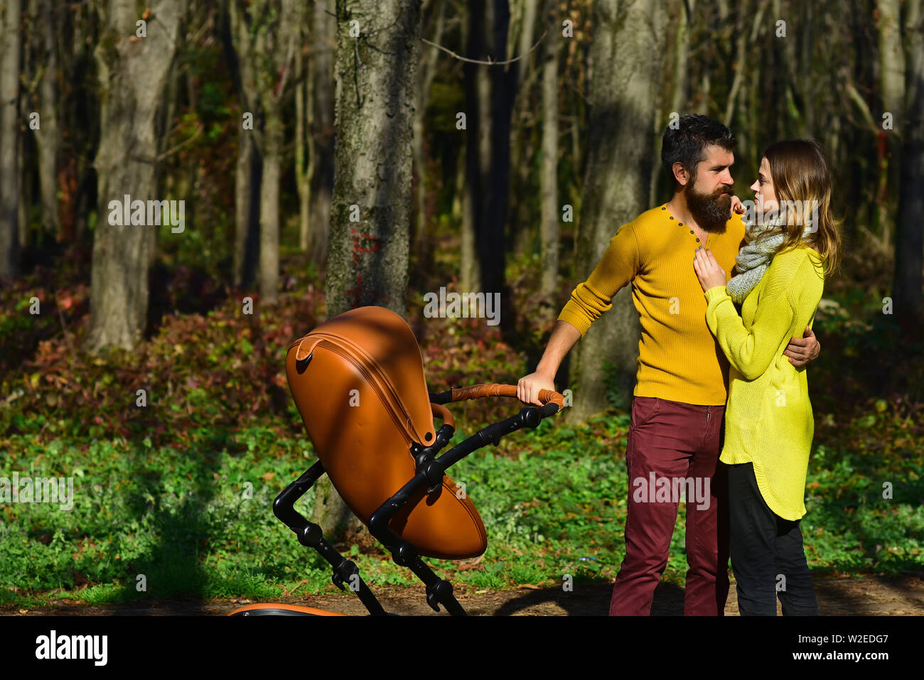 Family values concept. Loving husband kiss wife with baby pram in spring park, family values. A celebration of love and friendship. - Stock Image