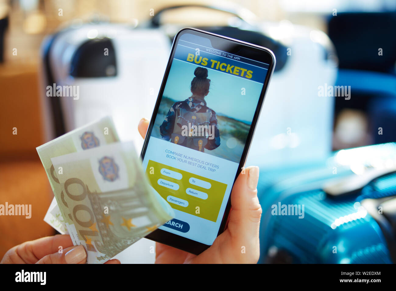 Closeup on female hand with smartphone near trolley bags at modern home in sunny hot summer day booking bus tickets online using app and holding money Stock Photo