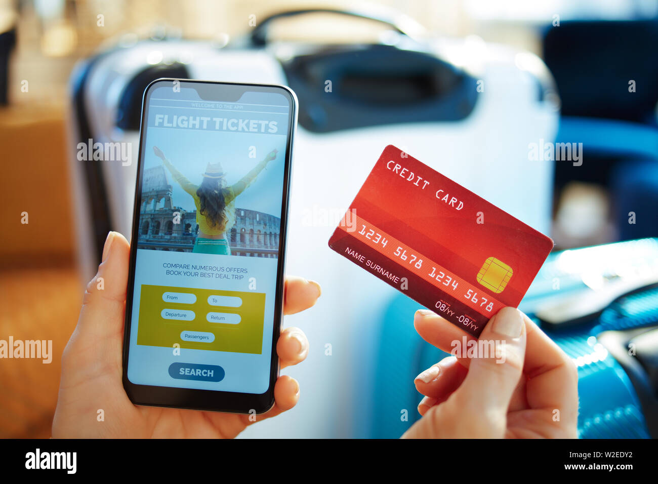 Closeup on female hand with smartphone and credit card buying plane tickets online using app near trolley bags in the modern house in sunny hot summer - Stock Image