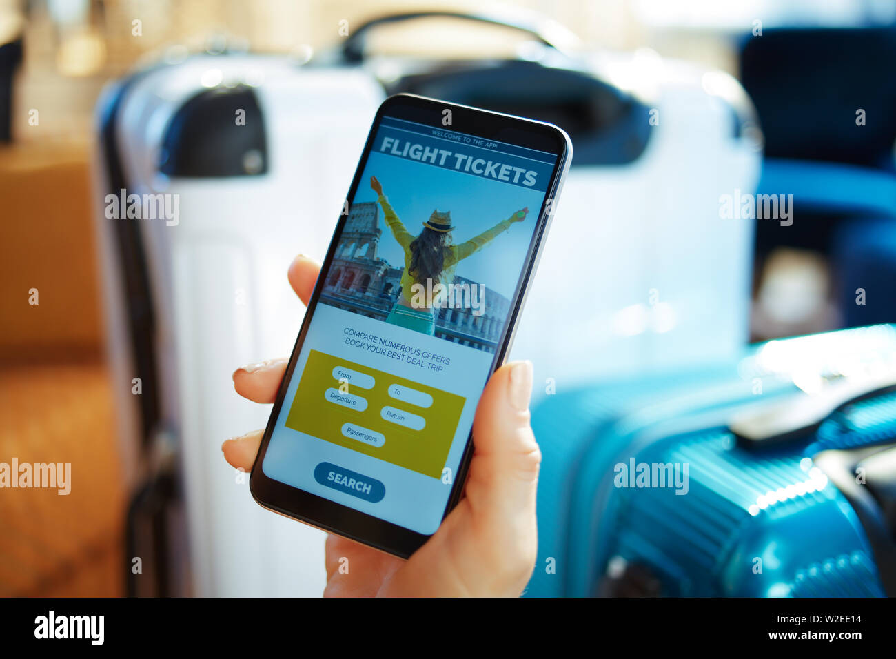 Closeup on female hand with smartphone near trolley bags at modern home in sunny hot summer day buying plane tickets online using app. - Stock Image