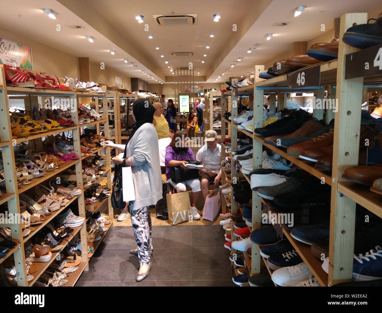 People shopping for shoes in a store - Stock Image
