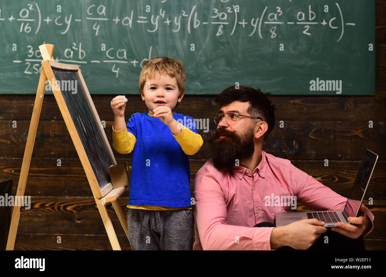 Kid reciting a poem while teacher listens attentively. Cool guy in pink shirt sitting on floor next to standing kid. Back to school. - Stock Image