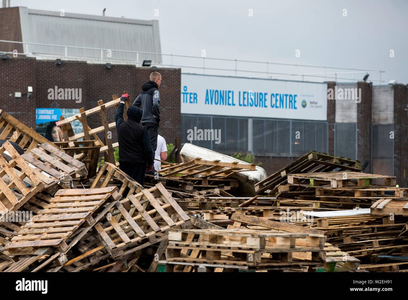 Men stand on an unlit bonfire as they begin to remove tyres and material of an July 11th night bonfire at Avoniel Leisure Centre shortly after a Belfast City Council committee voted to send contractors in to remove material. - Stock Image