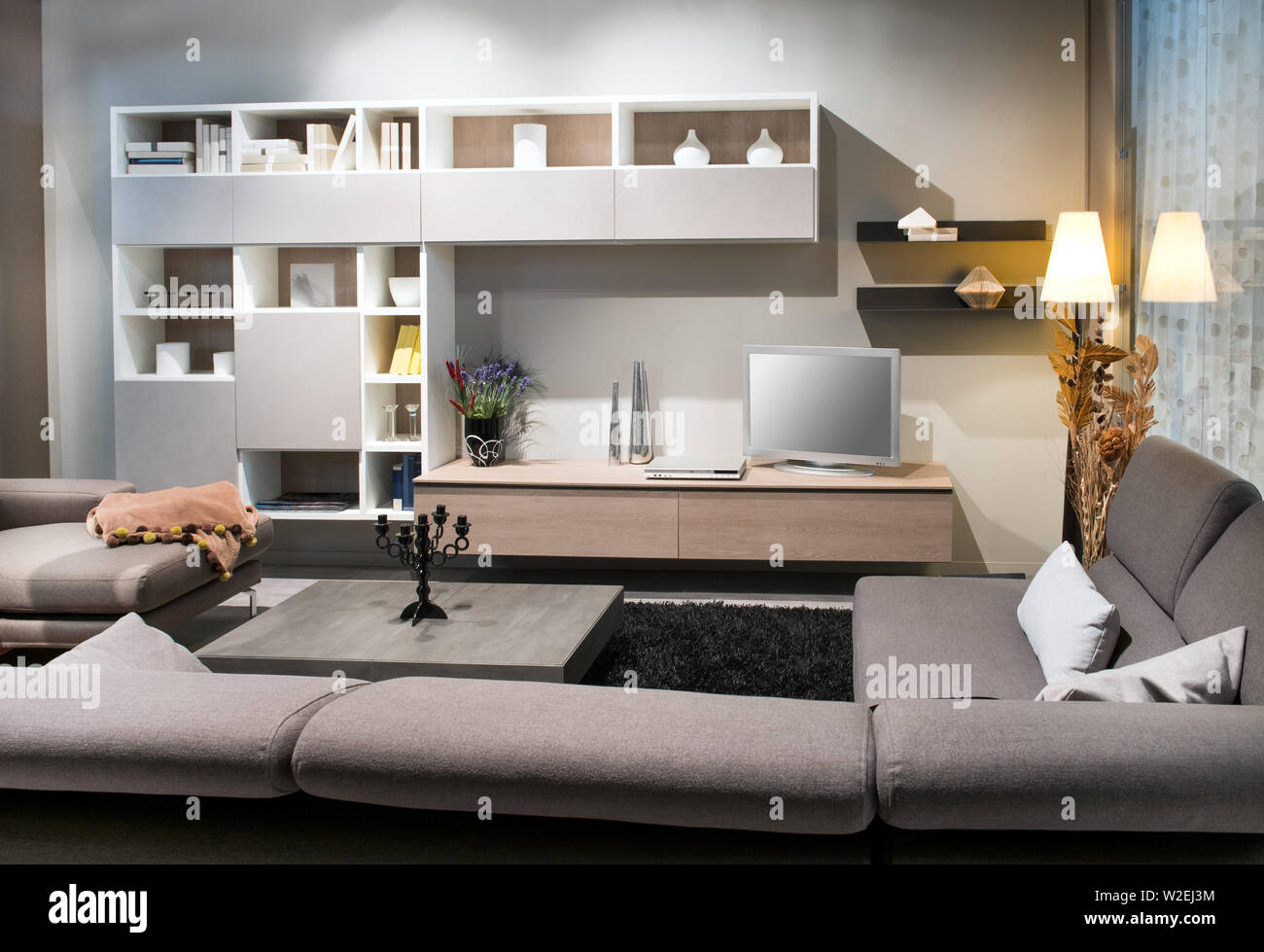 Modern living room interior with comfortable upholstered brown sofas facing a display cabinet and television illuminated by down lights and a lamp Stock Photo