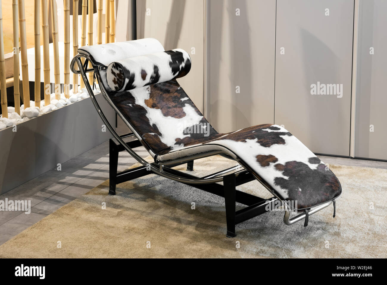 Elegant modern curved chaise longue with animal hide on a metal frame inside on a rug in a stylish home with neutral beige brown decor - Stock Image