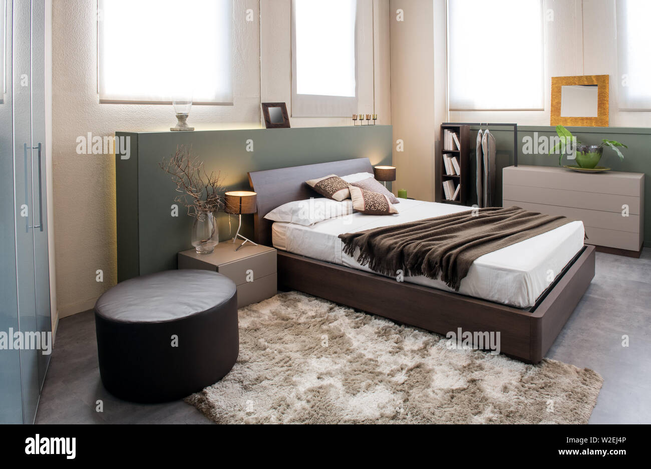 Modern luxury brown monochrome bedroom interior with large headboard above a double beds with cabinets, ottoman and built in wardrobe Stock Photo