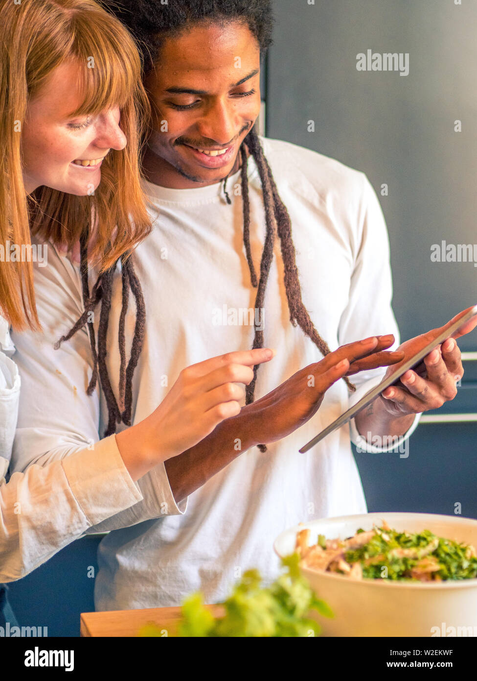 Interracial couple formed by African and Caucasian prepare a salad together with the help of their cell phone Stock Photo