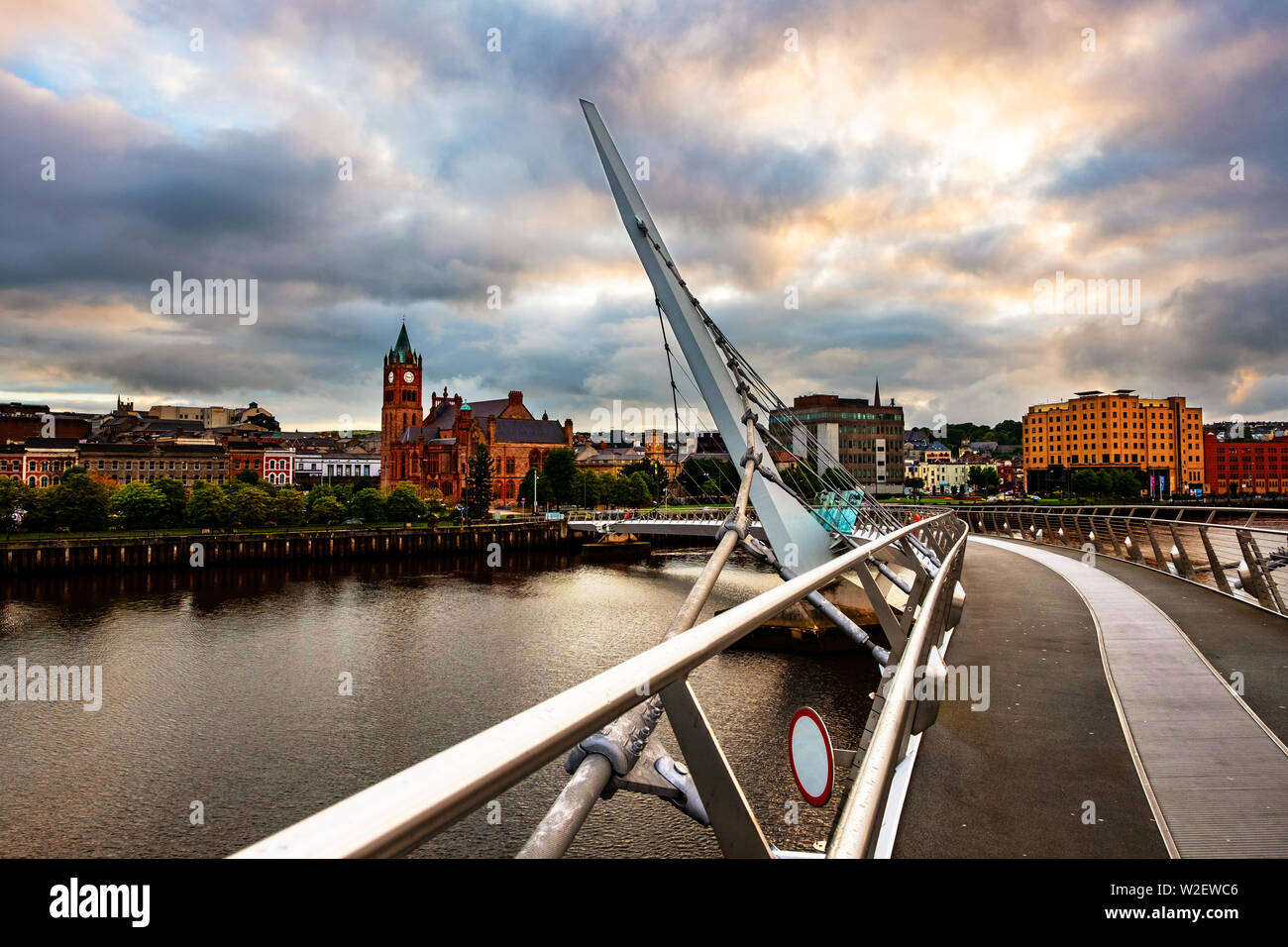 Derry, Northern Ireland. Peace bridge in Derry Londonderry in Northern Ireland, UK with city center at the background. Sunny evening with cloudy sky, - Stock Image