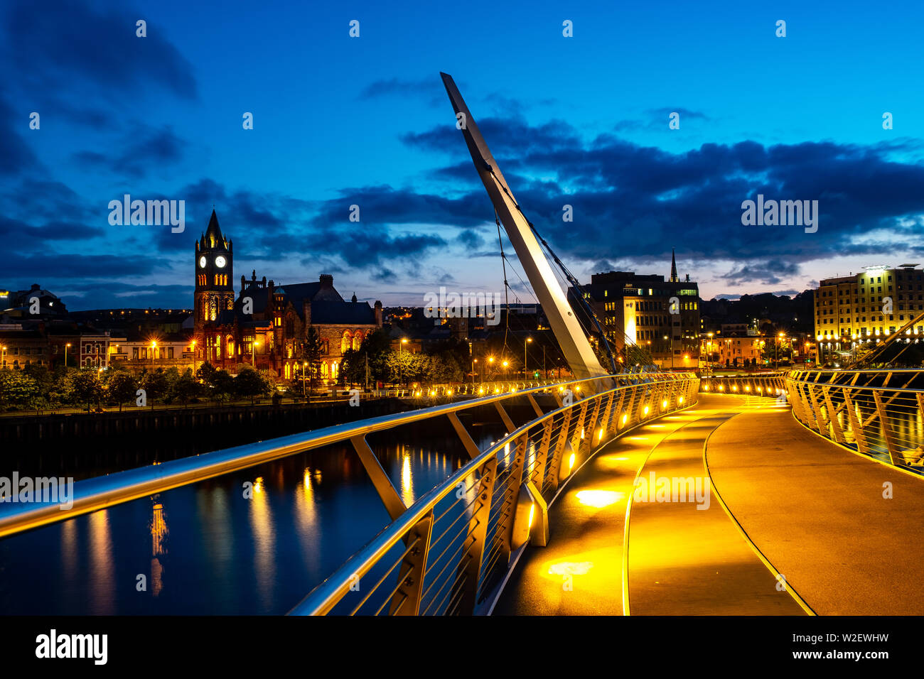 Derry, Northern Ireland. Illuminated Peace bridge in Derry Londonderry in Northern Ireland with city center at the background. Night cloudy sky, refle - Stock Image