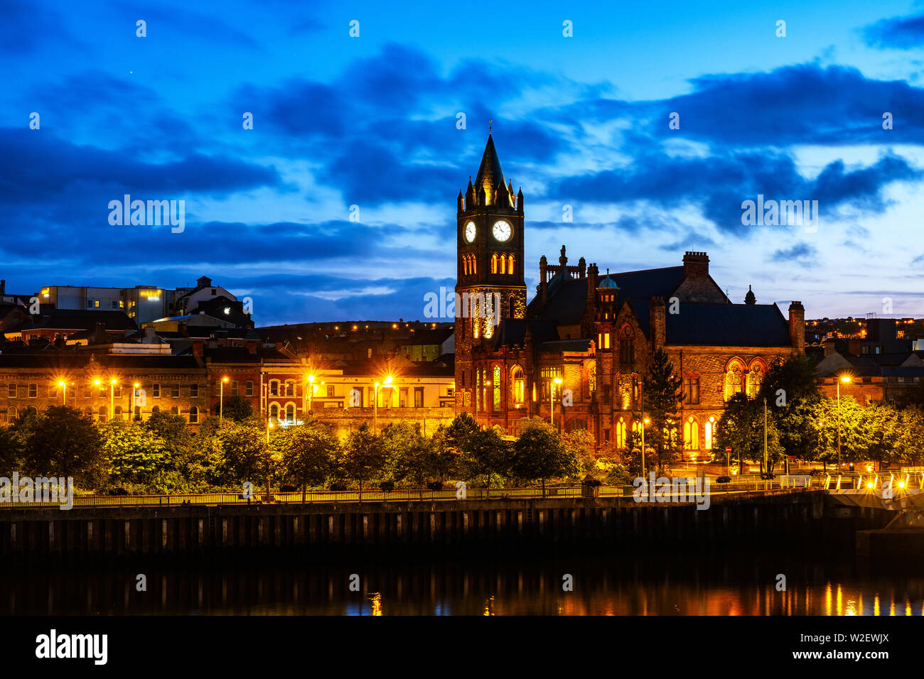 Derry, Northern Ireland. Illuminated Cathedral in Derry Londonderry in Northern Ireland with city center at the background. Night cloudy sky, reflecti - Stock Image