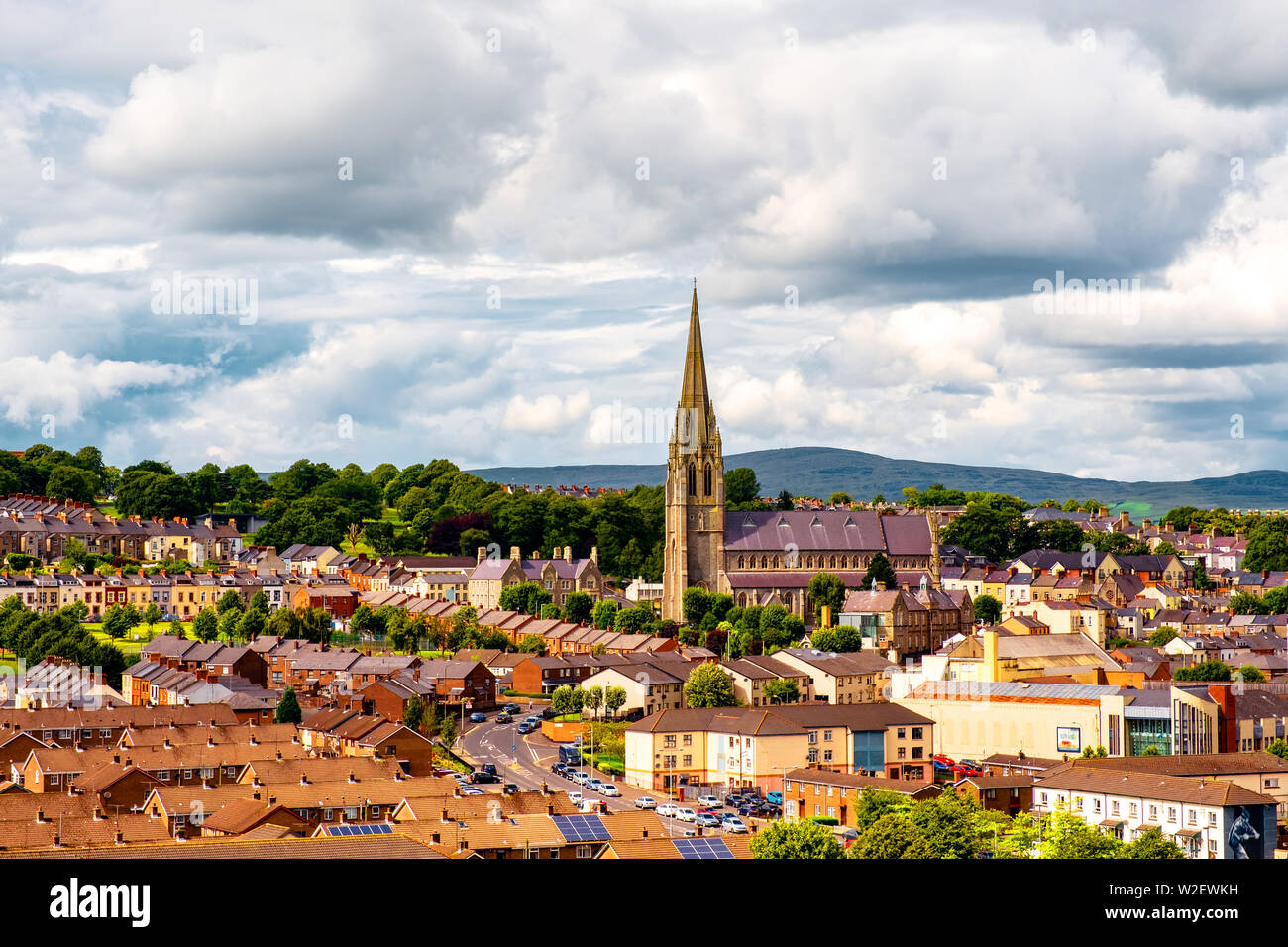Derry, North Ireland. Aerial view of Derry Londonderry city center in Northern Ireland, UK. Sunny day with cloudy sky, city walls and historical build - Stock Image