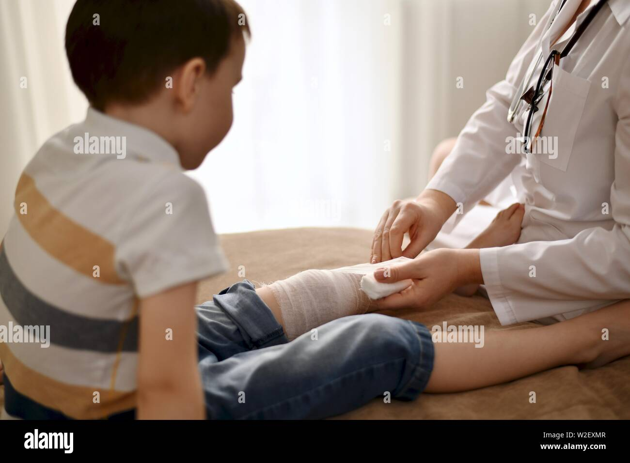 The doctor very carefully and carefully bandages the leg of the child sitting in front of her. The boy quietly watches what is happening. - Stock Image