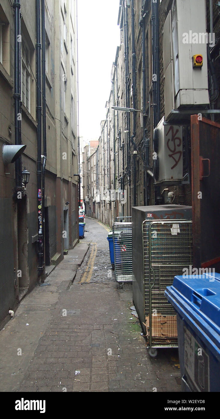 View south down Coutties Wynd, Dundee. The line of a medieval street, now a rear service road, lined with wheelie bins or dumpsters. Links Nethergate - Stock Image