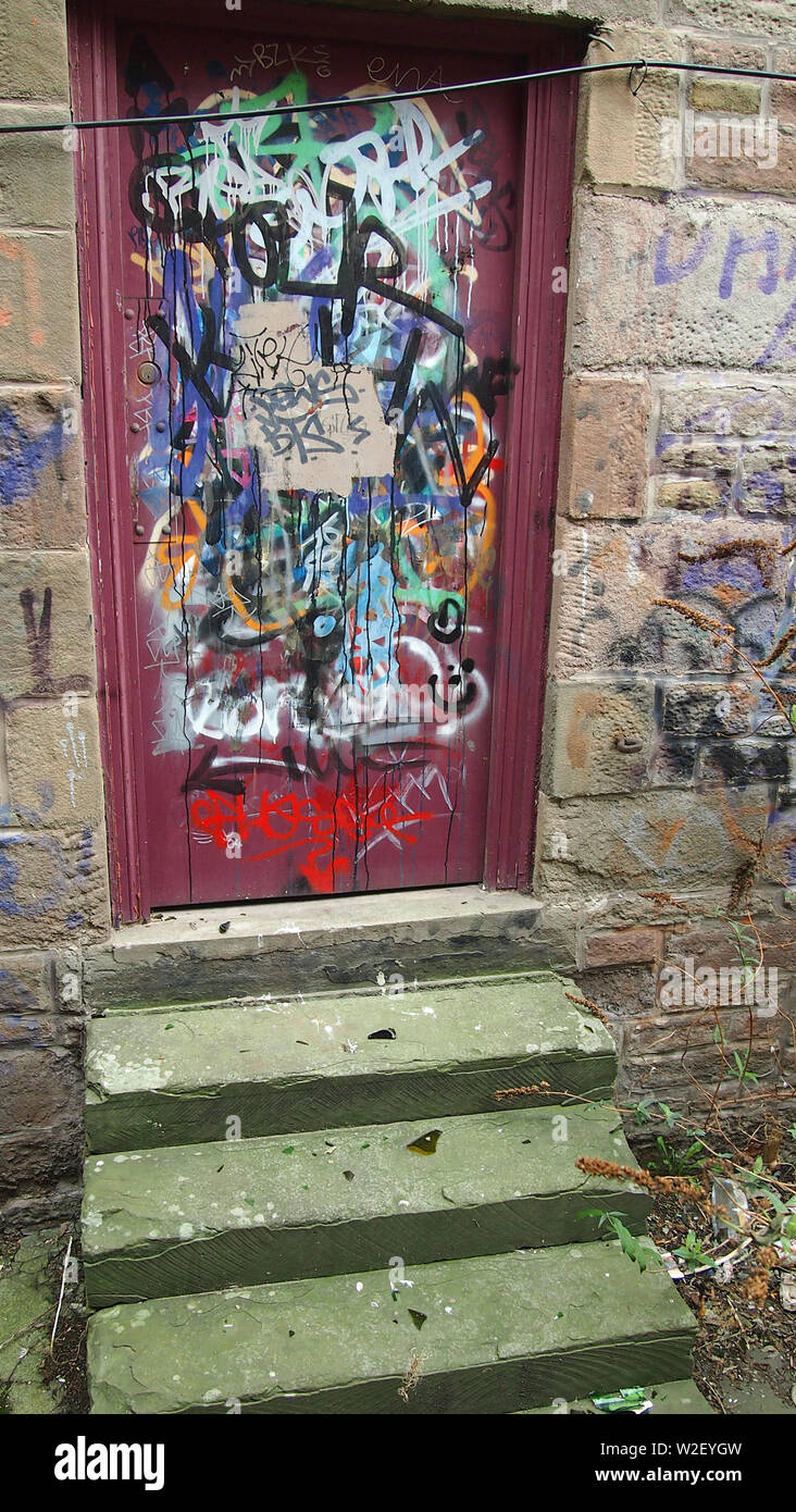Layers of grafitti on a wooden doorin Pullar's Close, Dundee, Scotland. Three steps lead up to the door. - Stock Image