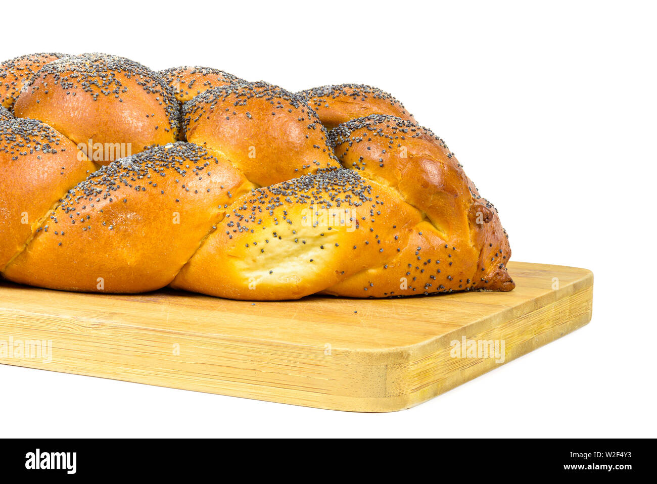 Closeup of fresh whole challah bread on chopping board isolated on white background with clipping path Stock Photo