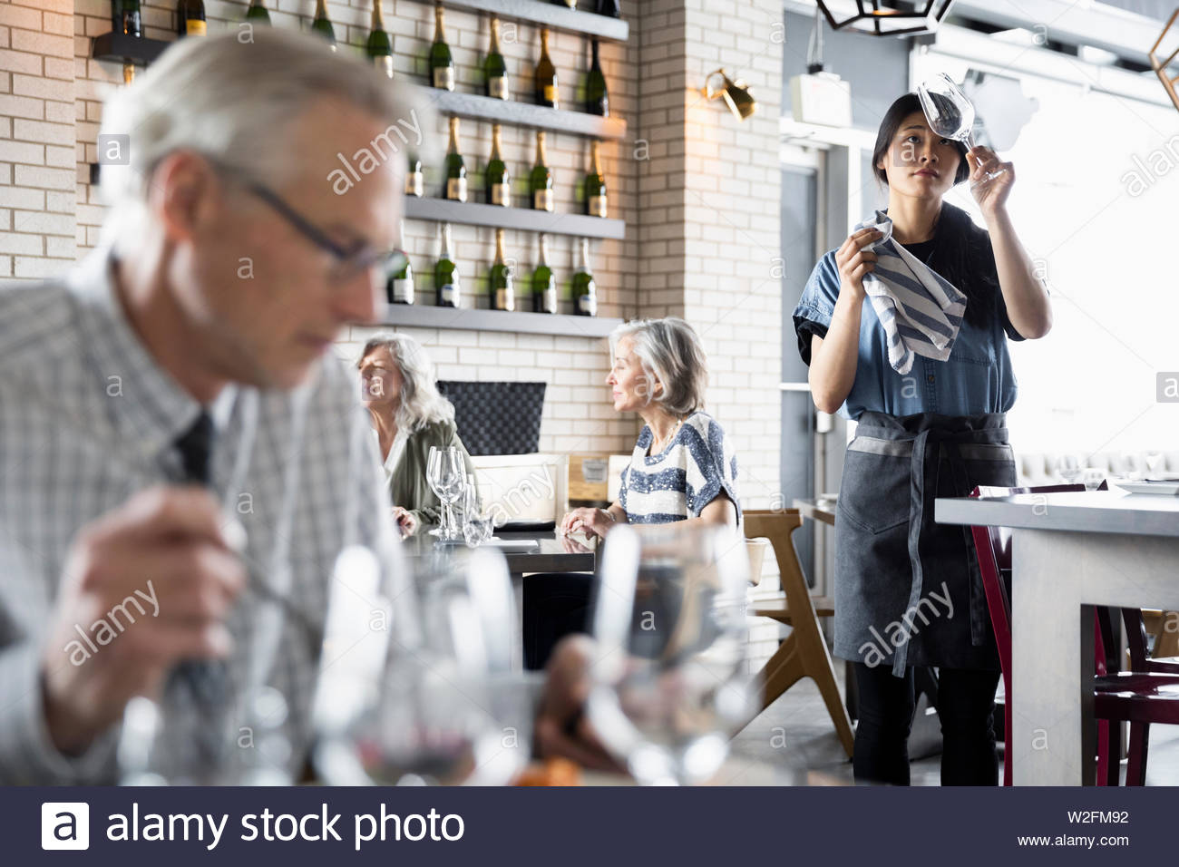 Waitress cleaning wine glasses in restaurant - Stock Image