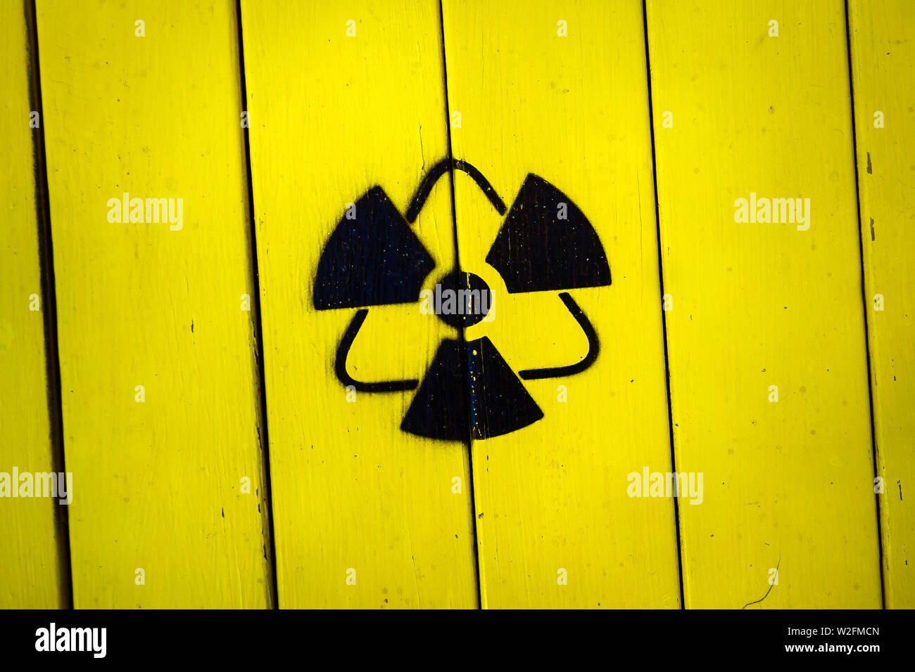 Sign of radiation on a yellow wooden board. - Stock Image