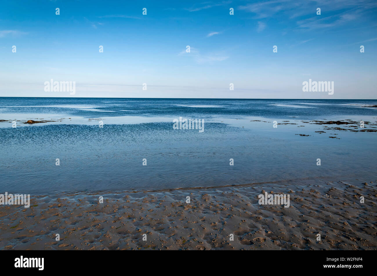 View out to the Irish Sea at low tide from a deserted Douglas beach, Isle of Man. - Stock Image