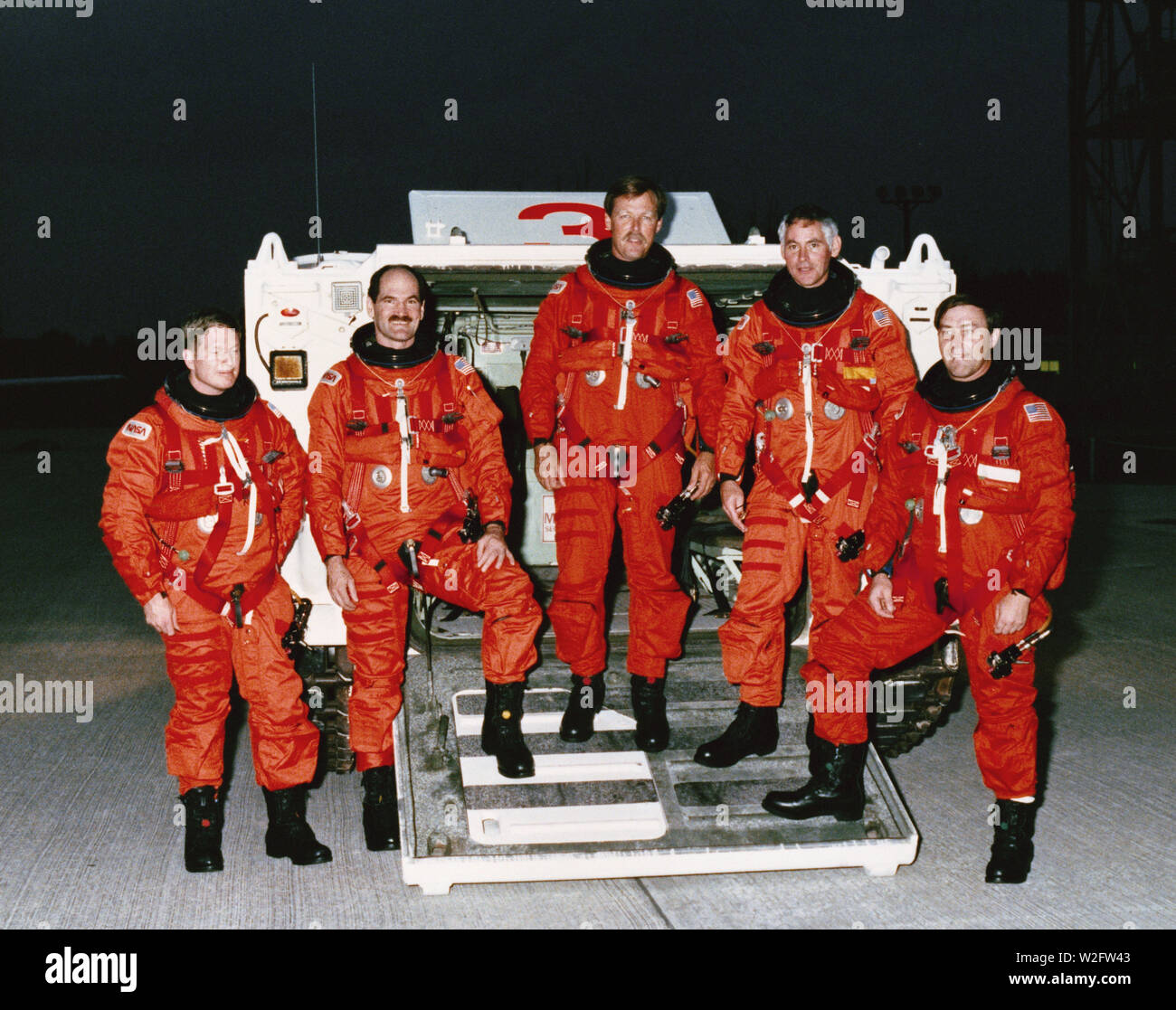 17-nov-1988-sts-27-atlantis-orbiter-vehicle-ov-104-crewmembers-participate-in-the-terminal-countdown-demonstration-test-tcdt-at-the-kennedy-space-center-ksc-standing-in-front-of-the-m113-tracked-rescue-vehicle-armored-personnel-carrier-apc-are-left-to-right-mission-specialist-ms-william-m-shepherd-pilot-guy-s-gardner-commander-robert-l-gibson-ms-richard-m-mullane-and-ms-jerry-l-ross-crewmembers-are-wearing-orange-partial-pressure-or-launch-and-entry-suits-les-W2FW43.jpg