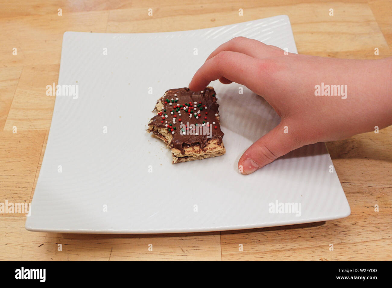A childs hand grabing a treat off a white plate Stock Photo